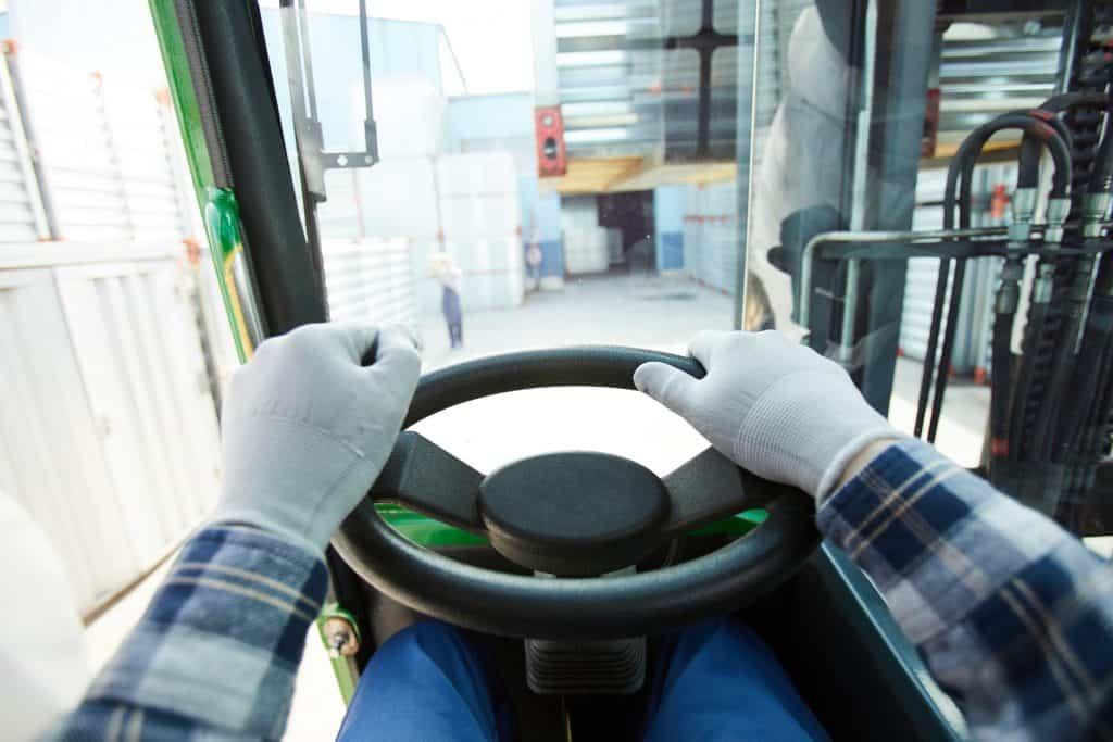 Forklift driver at steering wheel