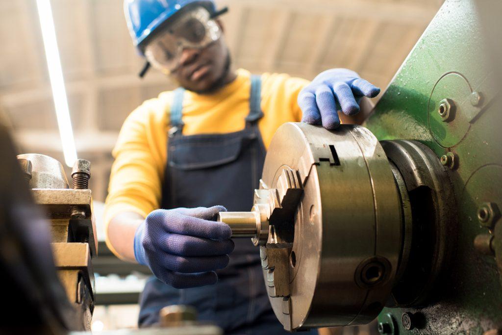 Machine operator adjusting machine